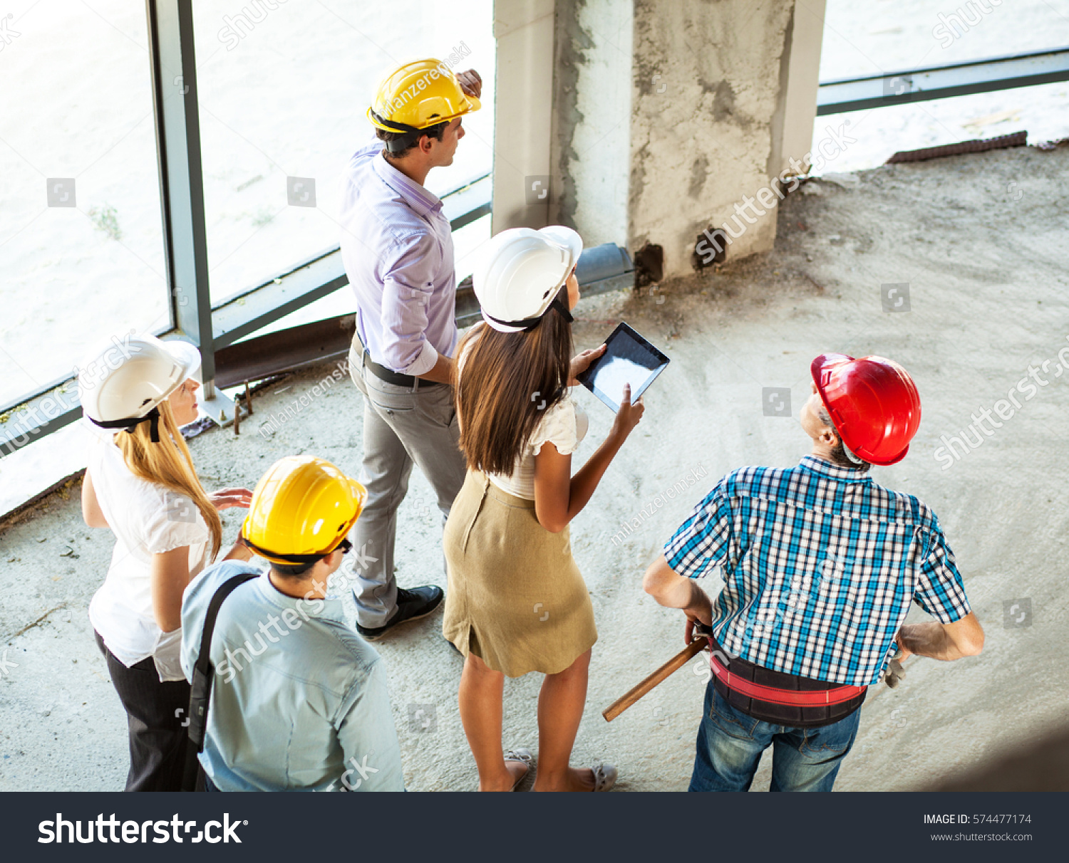 stock-photo-group-of-engineers-and-experts-discuss-about-construction-site-walking-through-building-site-574477174