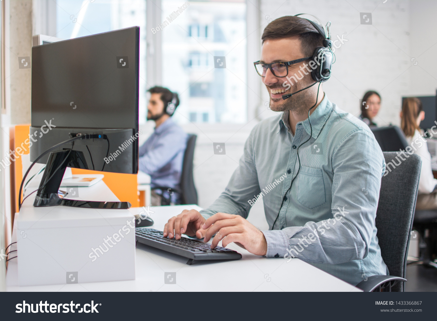 stock-photo-smiling-handsome-male-customer-support-phone-operator-with-headset-working-in-call-centre-group-of-1433366867